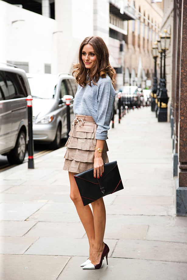 The fashion week street style regular teams a belted camel skirt with casual grey knit and envelope clutch for an effortless daytime look.