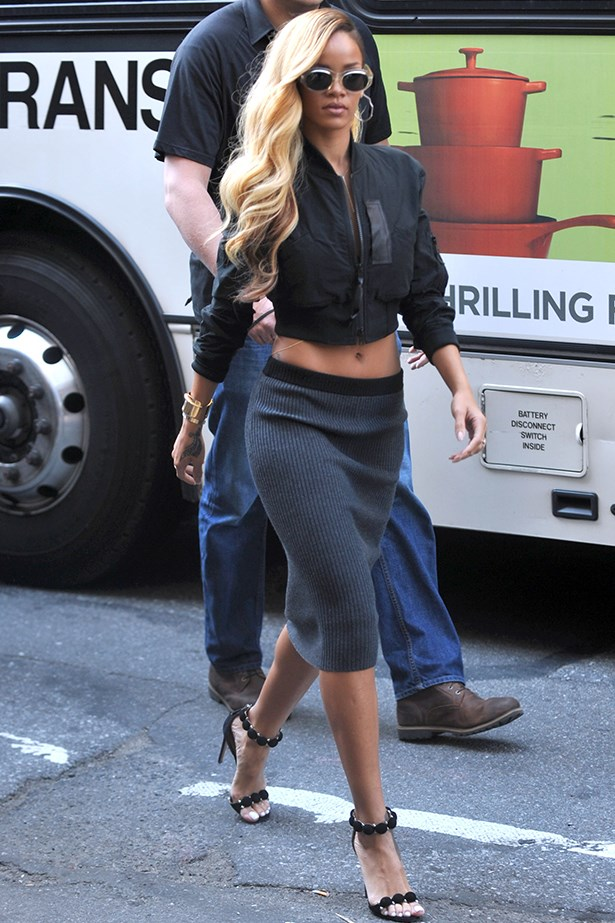 Rihanna wears a midriff baring bomber with a woollen skirt and black heels.