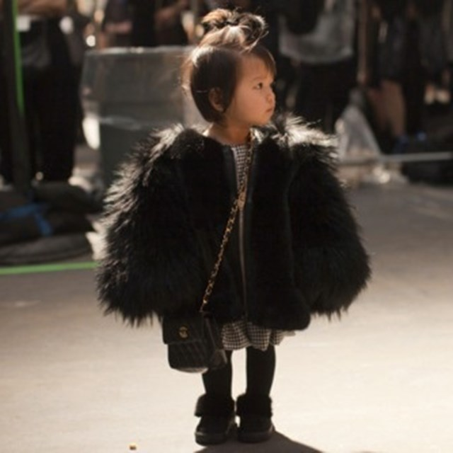 Flashback. The teeny tot turns up the drama wearing an oversized fluffy jacket and a Chanel purse.