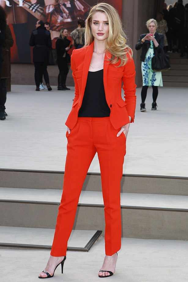 Clean-cut androgyny meets femme fatale as Rosie balances a bright red, tailored Burberry tuxedo with romantic side-swept tresses at Burberry Prorsum during London Fashion Week.