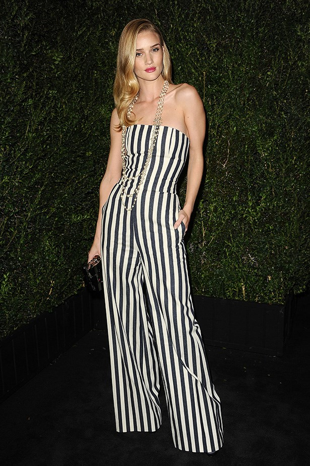 Perfectly on-trend in monochrome stripes, Rosie playfully pairs her Chanel jumpsuit with pearls, adding a touch of '20s flapper flair to her look at the Chanel pre-Oscars dinner in Los Angeles.