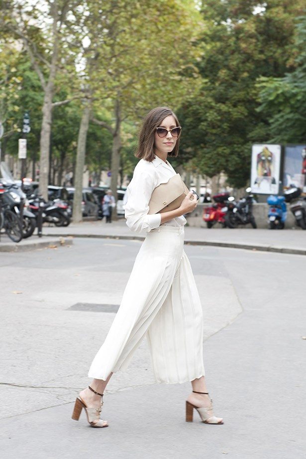 A Paris Fashion Week show goer opts for clean lines and a minimal colour palette with cream wide leg pants and a classic shirt.
