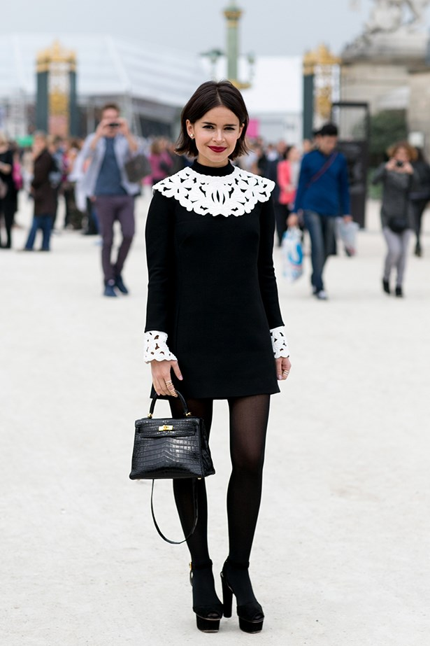 Russian street style royalty, Miroslava Duma wears a surprisingly demure black dress with white lace detailing at the Jardin Du Tuileries.