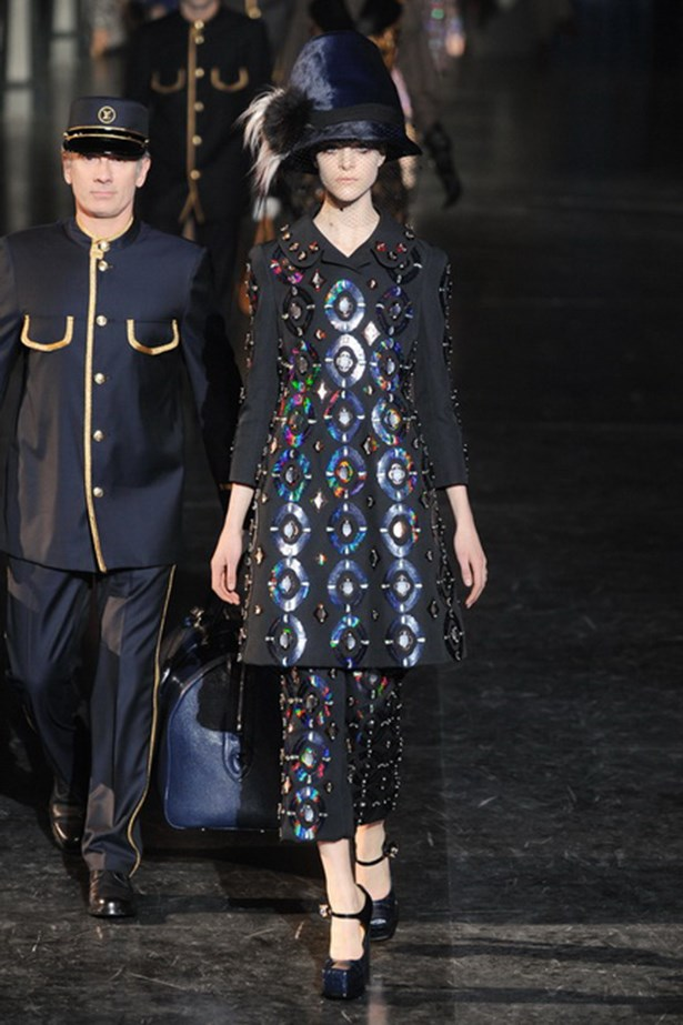 Marc Jacobs sent models down the runway in glittering coats and towering hats escorted by train attendants at the Louis Vuitton AW12 show.