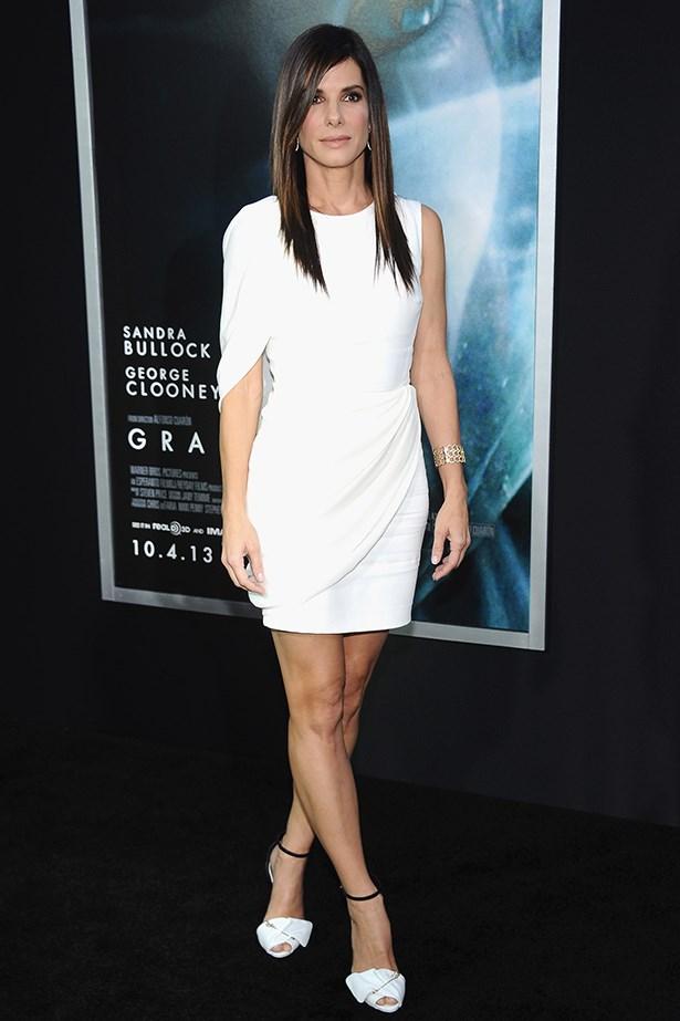 Sandra Bullock opts for a Giambattista Valli shoulder-drape dress and Giuseppe Zanotti heels.
