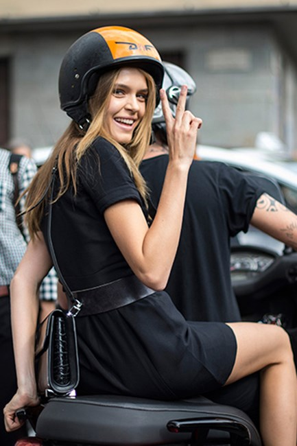 A model jumps aboard a vespa to avoid Milan Fashion Week chaos.