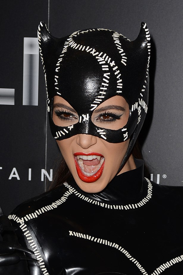 Kim Kardashian makes a great Catwoman with winged liquid eyeliner and bold red lipstick.
