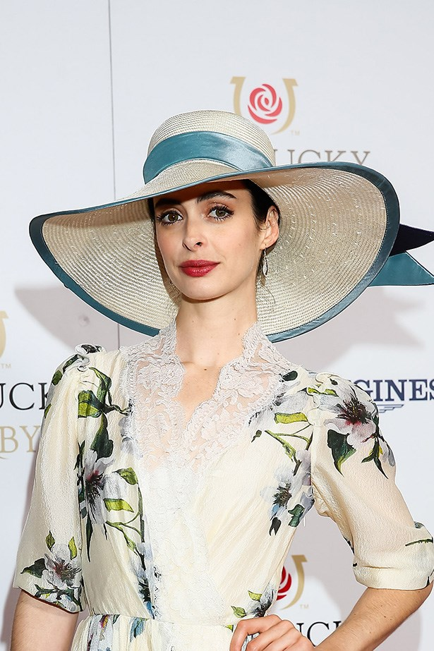 """IDE-BRIMMED: Krysten Ritter played with her """"Southern belle"""" look at the Kentucky Derby, accompanying her wide-brimmed sun hat with deep berry lips and softly lined eyes."""