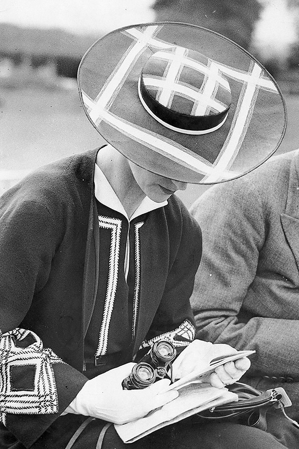 """<p><strong>Yeojin Bae</strong>: """"Think practically – I learned the hard way a few years back that a full vintage tulle headpiece over my face means I can't really eat or drink!""""</p> <p>CIRCA 1937: Woman with hat and binocular at a horse race. Photograph, 1937</p>"""