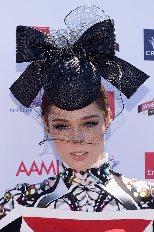 Never one to shy from making a beauty statement, Coco Rocha wears dramatic winged eyeliner, and thick false lashes – defining her eyes under a jaunty hat and veil.