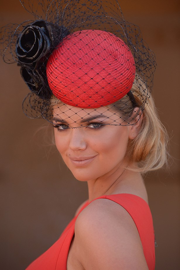 Kate Upton's SIZZLING smoky eye, bronzed complexion, and nude lip complements her fiery red dress and hat.