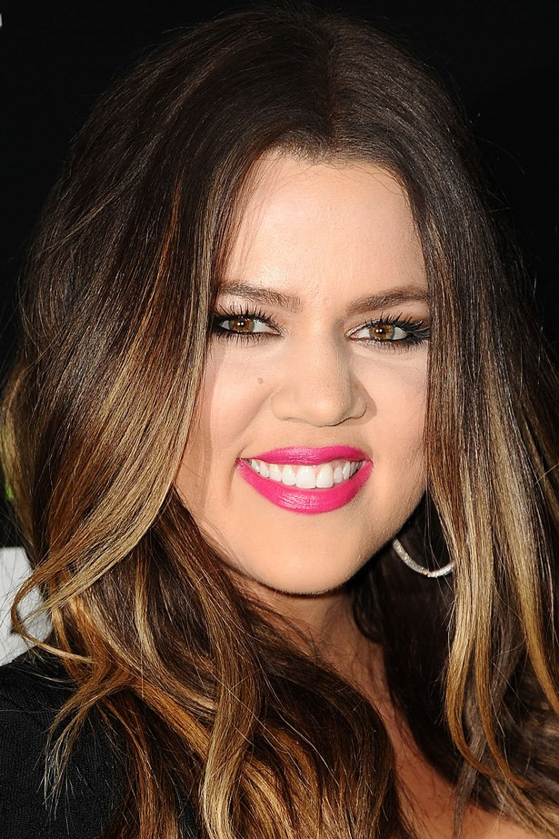 Khloe Kardashian wears fuchsia pink lips paired with full brows and lashings of mascara.