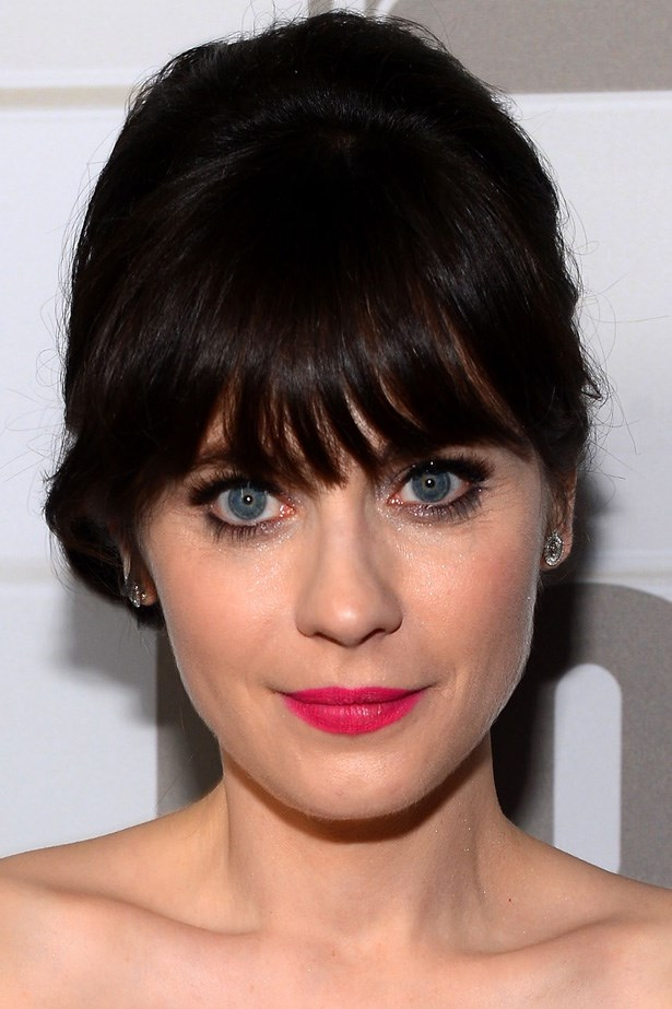 Zooey Deschanel combines her trademark heavy bangs with a statement hot pink lip at the Emmy's.