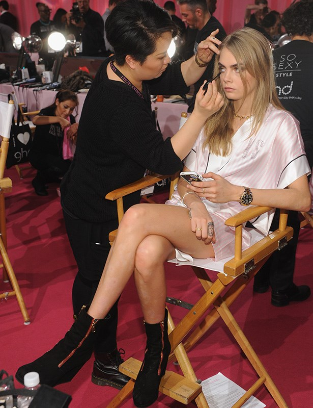 Cara Delevingne having her make-up done backstage