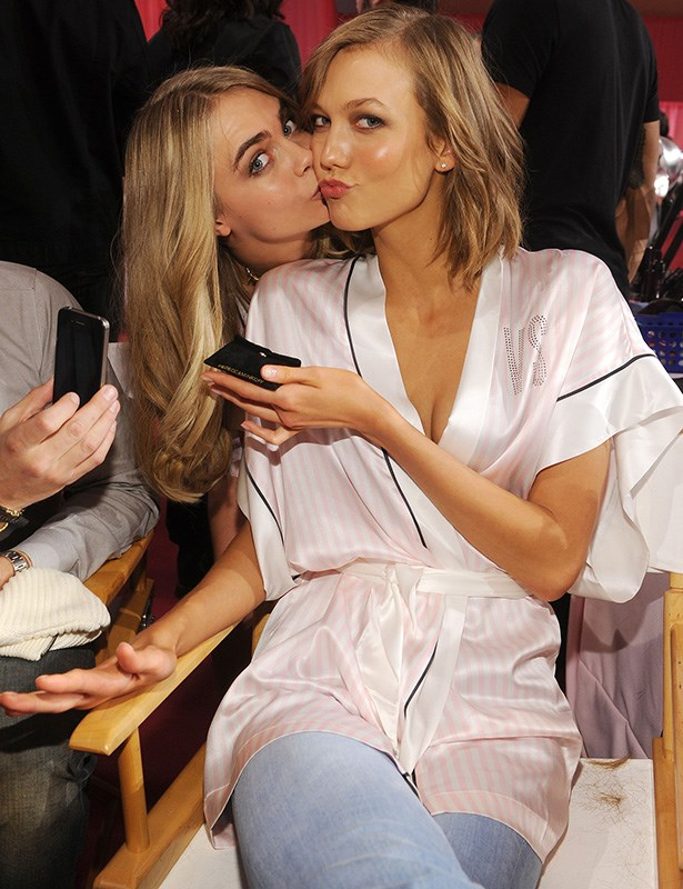 Cara Delevingne and Karlie Kloss sharing a kiss on the cheek backstage