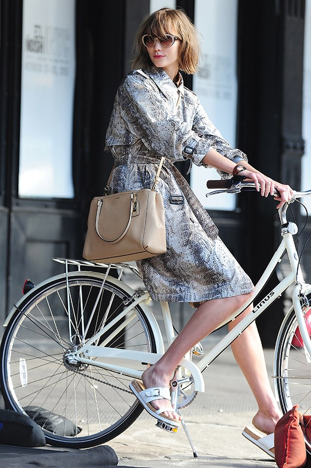 American beauty Karlie Kloss looks cycle-chic in a molten trench coat and taupe shoulder bag.