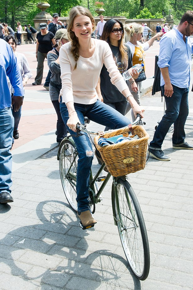 Behati Prinsloo cycles in Central Park wearing a pastel sweater and blue jeans.