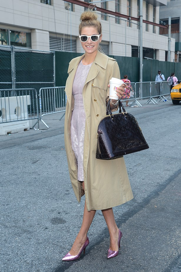 Sydney-born model Jessica Hart wears her hair in her trademark dishevelled high bun, paired with a trench coat and metallic heels.