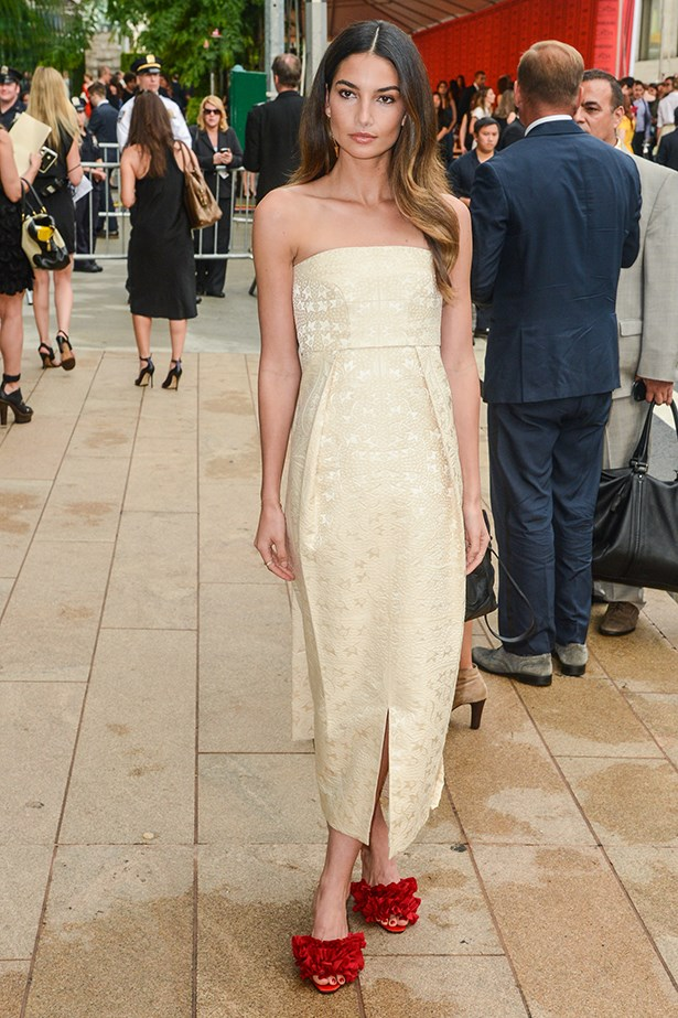 Aldridge wears a strapless dress and red floral appliqué heels by The Row.