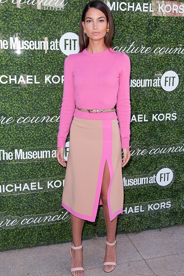 Aldridge wears a neon pink and beige outfit by Michael Kors, pared back with nude sandals.