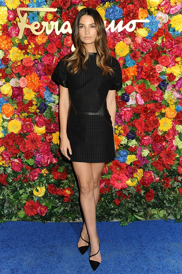 The model demonstrates exactly how to wear a little black dress in a Salvatore Ferragamo quilted leather dress and Christian Louboutin heels.
