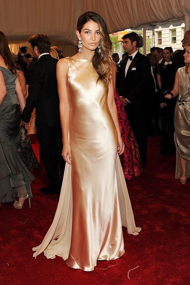 Aldridge wears a nude silk Ralph Lauren dress with statement earrings to the 2011 Met Gala.