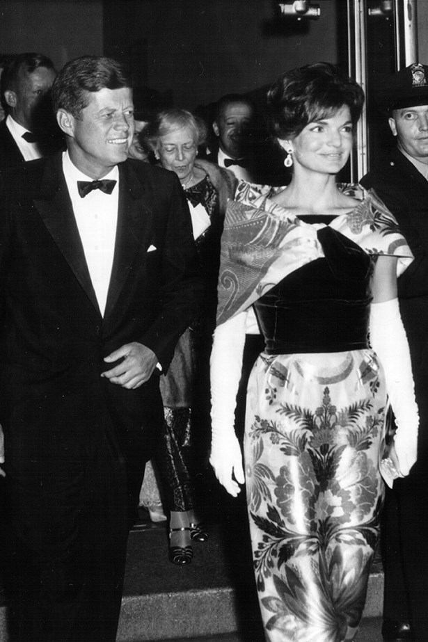 The First Lady wore an elegant two-piece with a matching floral cape as she left a theatre with President Kennedy in Washington, 1962.