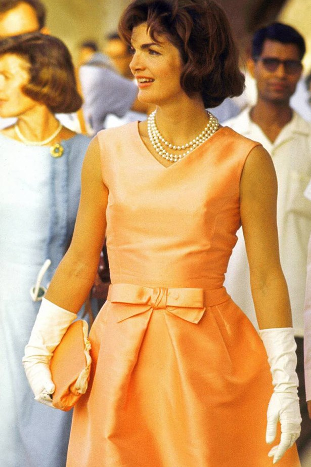 On a visit to India in 1962, the First Lady wore a fitted apricot silk dress and a triple strand of pearls.