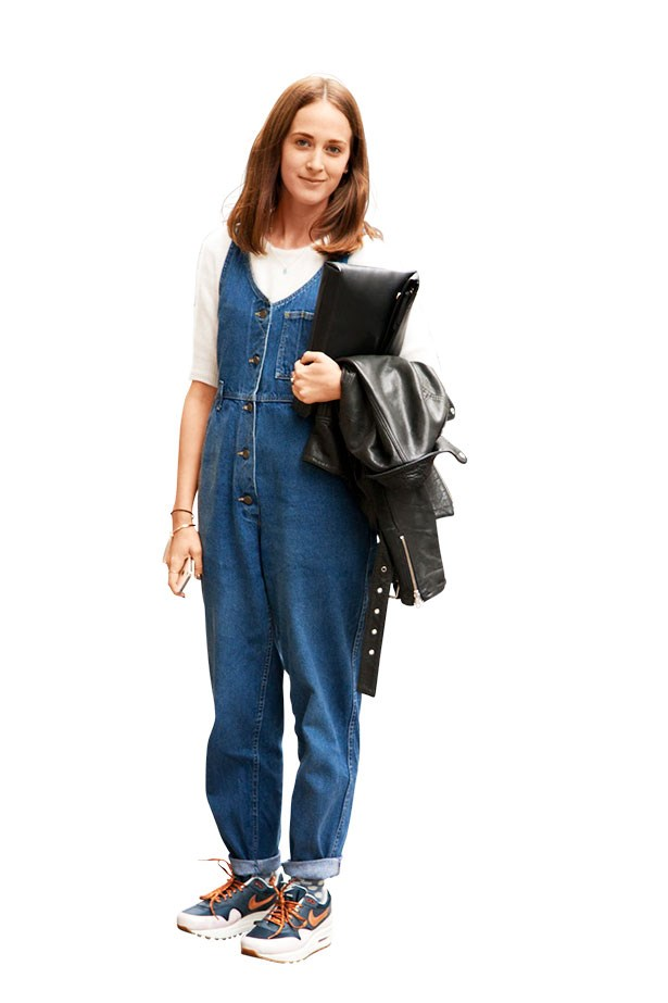 A show goer wearing dungarees and trainers to London fashion week