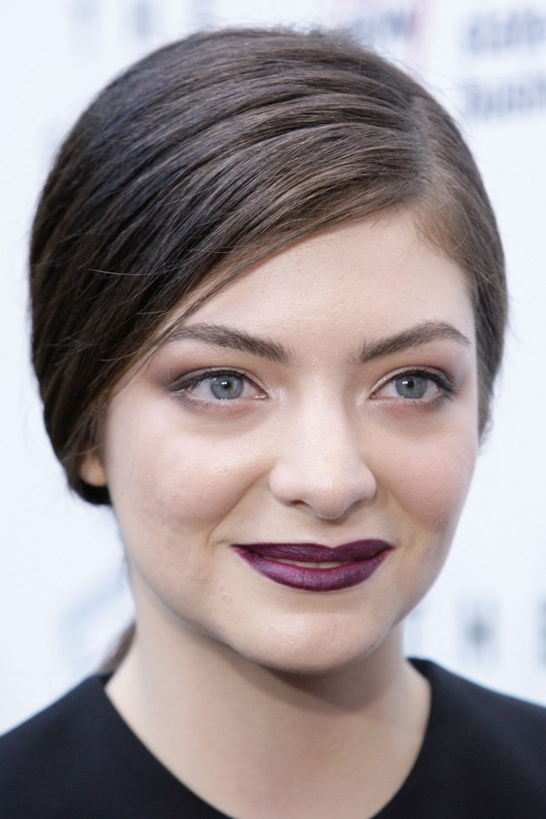 Lorde shows a slightly demure side with a natural side swept pony tail and lightly lined eyes.
