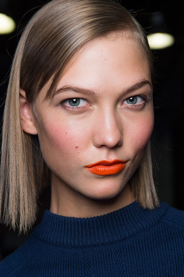 Go for a bright pop of colour with orange lipstick, as seen at DKNY's SS14 show. It instantly makes anyone look tanned and glowing – helped by a touch of peachy blusher.