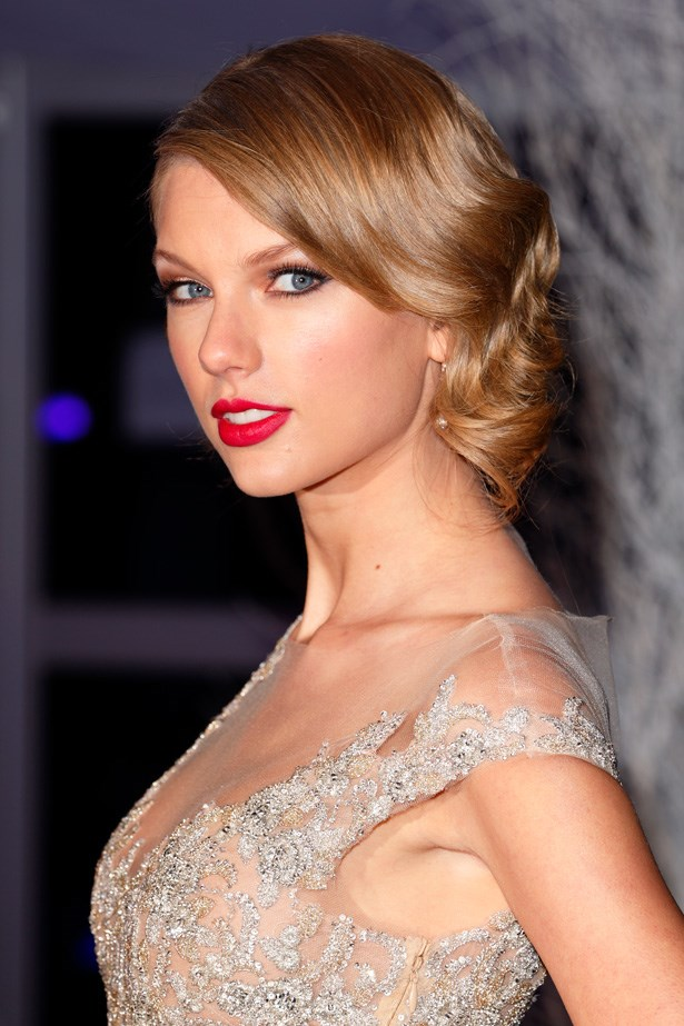 Attending an event at Kensington Palace, Swift looks royally chic with an elegant twisted 'do and her trademark red lip.