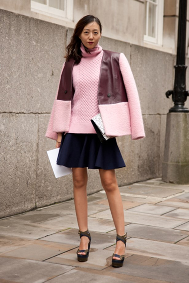 A fashion week goer in a pink knit and jacket with a skater skirt