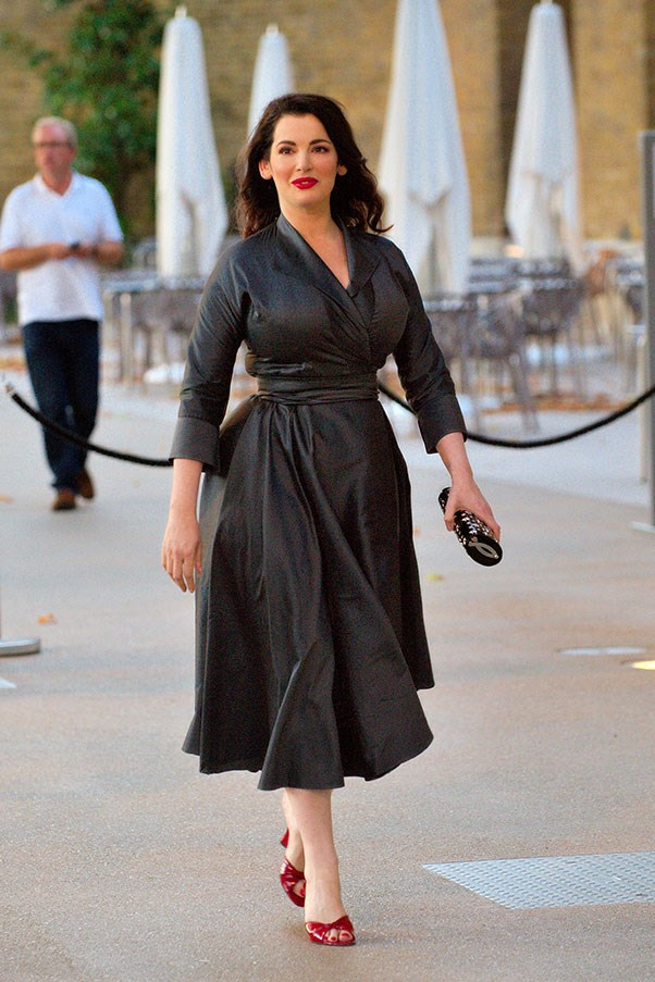 For a bolder evening look, Nigella wears a dramatic, flared dress with pops of red on her shoes and lips at her then-husband Charles Saatchi's book launch in 2009.