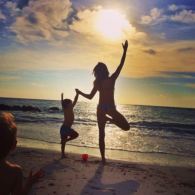 """Bündchen does her best earth mother impression in this snap, which shows her practising yoga with four-year-old son Benjamin on a beach somewhere. """"Good morning! Sending much love to all... #grateful,"""" she captioned it."""
