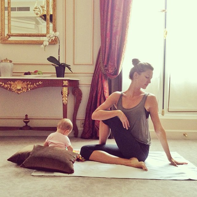 """""""Practicing yoga with my little partner before going to work,"""" says Bündchen. Because this photo isn't at all staged."""