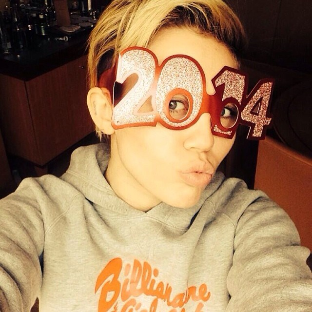 """Before Miley Cyrus took to the stage to perform a New Year's Eve concert in New York City, the singer donned these glasses and told us what to expect from the New Year: """"Yo 2014! If you ain't scuuuurd of me just ask 2013 what's up,"""" said the caption (@mileycyrus)."""