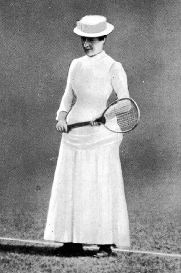 Rumour has it that the reason for wearing white is that it masks perspiration, but we don't think any bodily fluids are getting through those layers. Here, in 1884, the first women's champion of Wimbledon Maud Watson wears a corseted dress with a sweeping skirt and hat. (We hope it was secured tight!)
