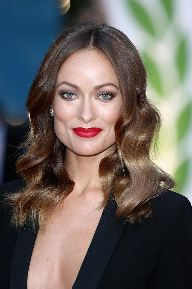 Olivia Wilde's middle-part glossy waves and eye makeup at the Rush World Premiere are channelling a '70s vibe – the low cut dress helps.