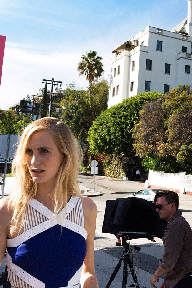 """Delevingne poses outside the Chateau Marmont in a design by David Koma. """"The dress is based on one of my favourite looks from SS14,"""" says Koma. """"The collection was inspired by the Japanese art of Kyudo. The dress, engineered from thick jersey, features waist cut-outs with protective lacing framed in leather."""" Photo: Andi Elloway"""
