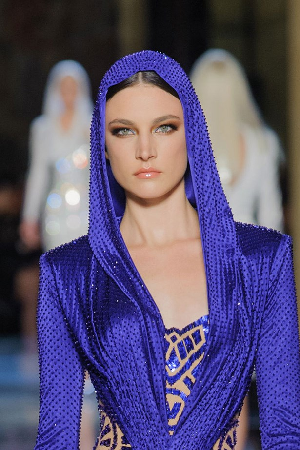 Atelier Versace Sporting metallic bronze lids and glossy lips, a hint of sky blue in the inner eye corner adds a surprising twist to the model's looks. Long, fluttery lashes are compulsory.