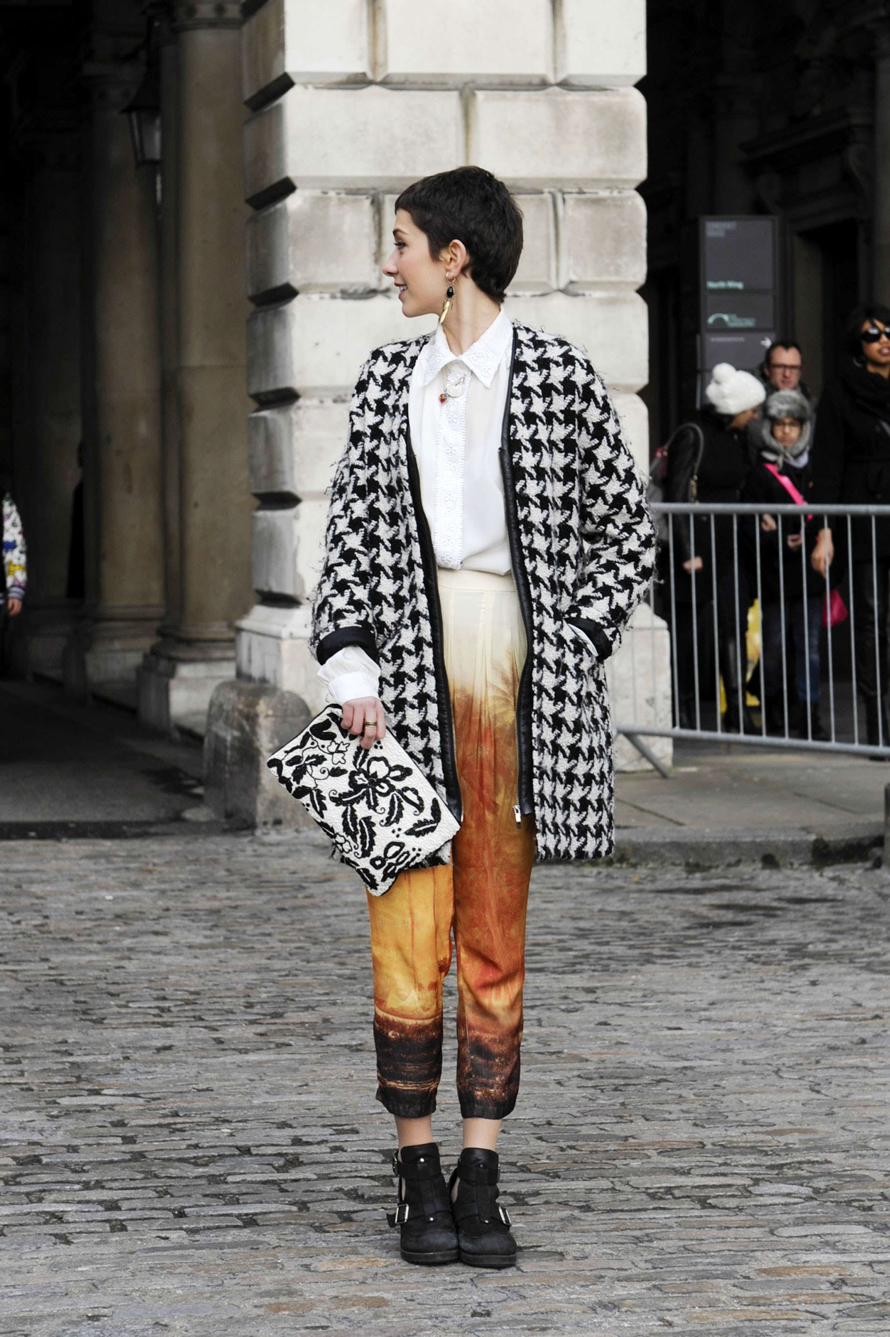 Clashing houndstooth with printed pants and a floral clutch gets a stylish tick of approval