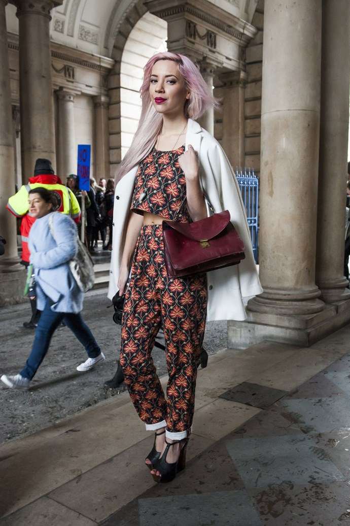 A luxe white coat and sky-high black platform wedges add refined class to the risk of a cropped print singlet and matching pants ensemble; burgundy tones carried through lips, bag and hair complete the look.