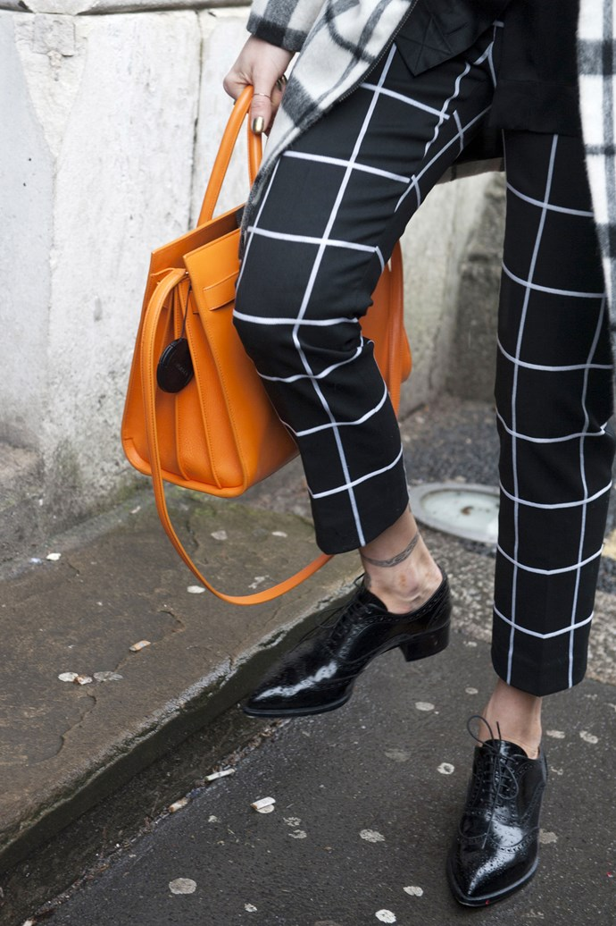 The simplicity of geometric pants and coat are uplifted by the bright orange tote and classic high gloss brogues