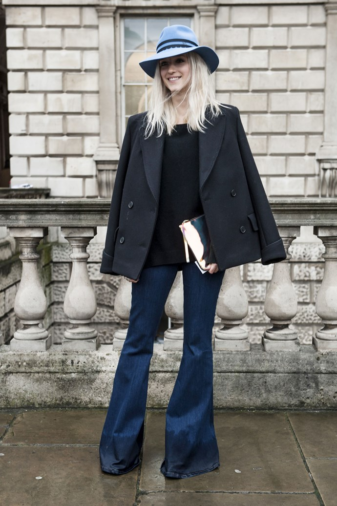 Angles are accentuated with the flare of wide-cut jeans and boxy black thick lapel coat, teamed with a baby-blue brimmed hat and mirrored finish clutch for stylish balance.