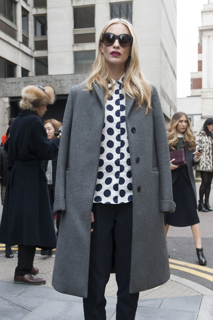 Poppy Delevingne playing it cool outside the shows in polka-dot, black pants and a grey marle coat light swung over her shoulders