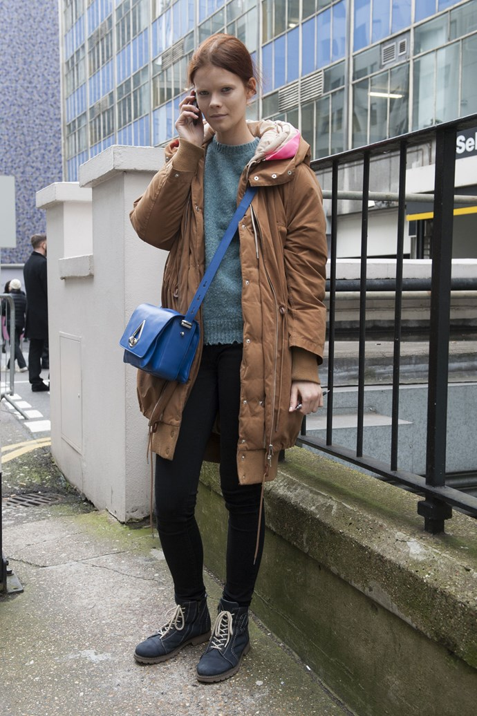 A model dressing down post show in a camel coat, jeans, lace-up shows and a blue over the shoulder bag