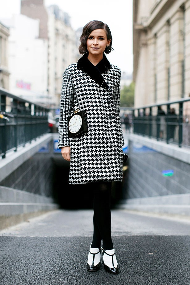 """Befitting of the season of contrasts, a houndstooth check coat is updated with a kooky clock bag and two-tone booties for an interesting spin on a classic."""