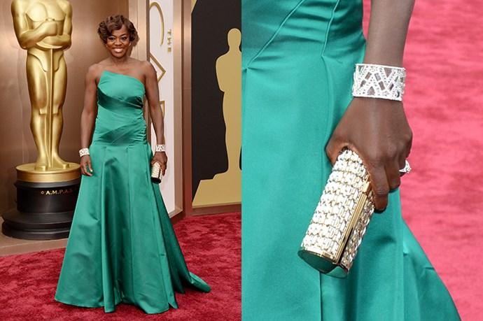 Viola Davis wears a pair of diamond cuffs, and carries a diamante-covered box-clutch purse with an Escada emerald-green gown.