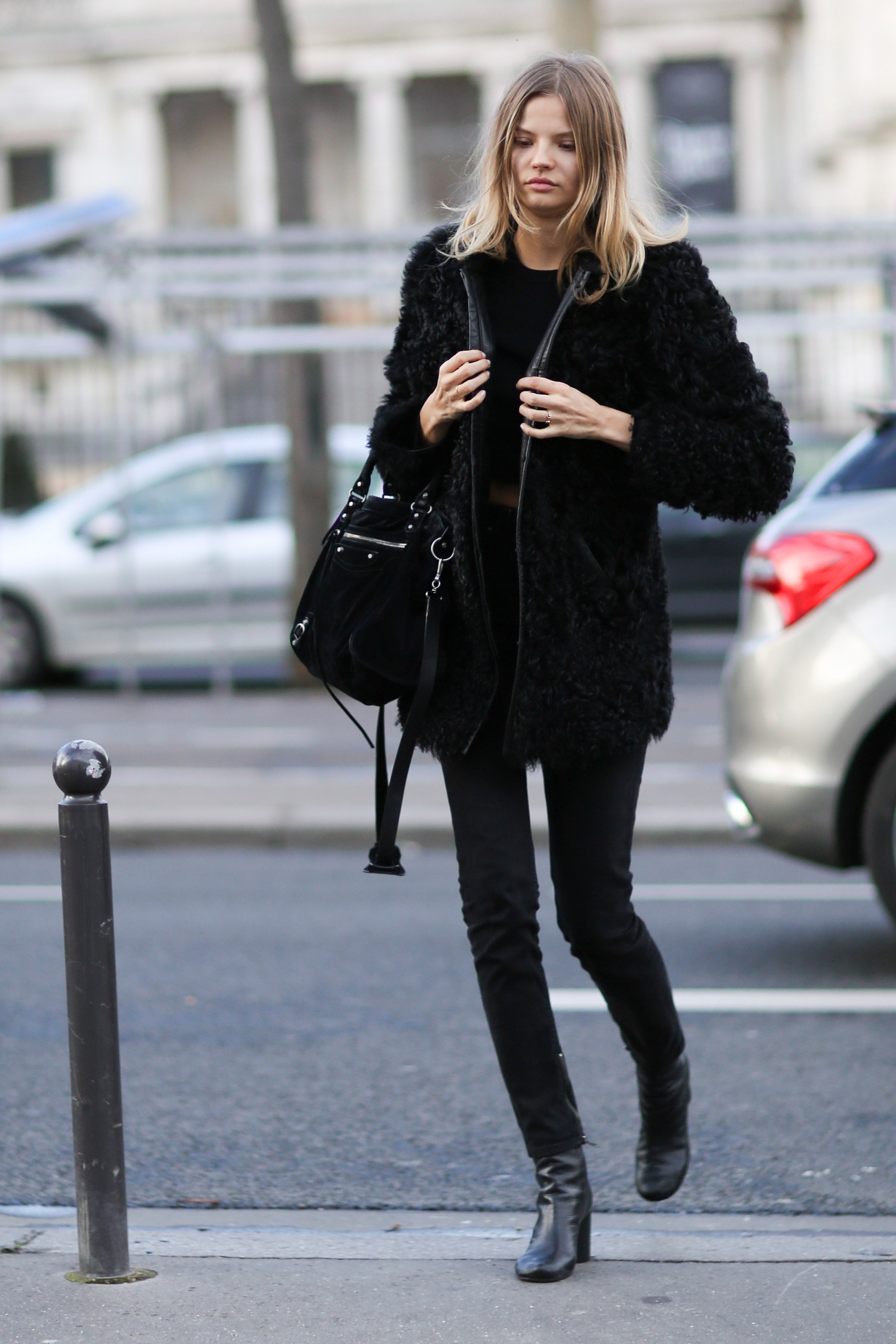 Magdalena Frackowiak radiates off-duty chic in black cigarette denim and a voluminous shearling coat.